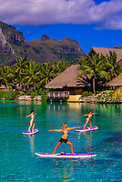 Women doing Standup paddleboard yoga in the lagoon, Four Seasons Resort Bora Bora, French Polynesia.