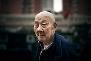 Old bald chinese man near the Suzhou River in Shanghai, China