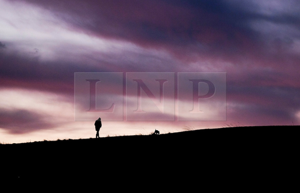 © Licensed to London News Pictures. 25/01/16<br /> Marske-by-the-Sea, UK. <br /> <br /> Early morning clouds dramatically lit by the sunrise are seen over Marske by the Sea as a man walks his dog along sand dunes.<br /> Remnants of Storm Jonah are expected to bring weather disruption to parts of the country over the next few days.<br /> <br /> Photo credit : Ian Forsyth/LNP