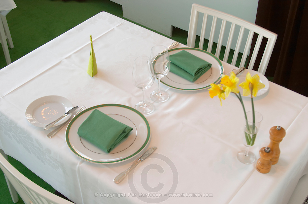 A restaurant table with a white linen table cloth set for two person, with plates, silver cutlery and green napkins and a yellow Easter daffodil lily flower on the table. Ulriksdal Ulriksdals Wärdshus Värdshus Wardshus Vardshus Restaurant, Stockholm, Sweden, Sverige, Europe