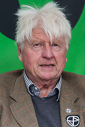 """London, UK. 9 October, 2019. Stanley Johnson, father of Prime Minister Boris Johnson, wearing an Extinction Rebellion sticker, prepares to address climate activists from Extinction Rebellion in Trafalgar Square on the third day of International Rebellion protests. He commented that the Prime Minister's characterisation of the protesters as """"uncooperative crusties"""" had been made in jest and described their work as """"extremely important""""."""