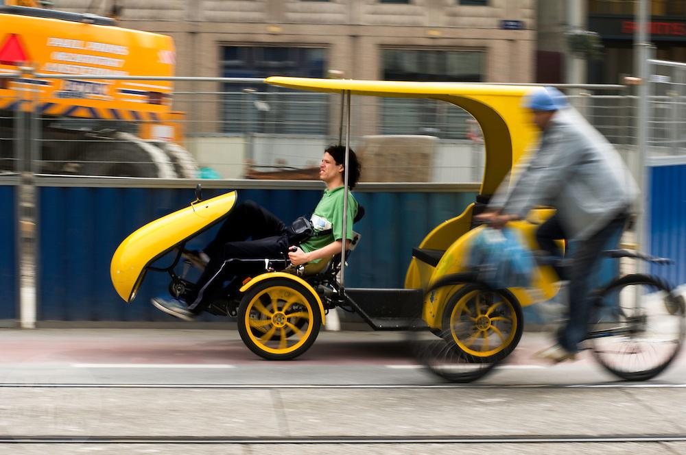 Een gele fietstaxi wordt op het Rokin in Amsterdam ingehaald door een man op een mountainbike.<br /> <br /> A man in a yellow bicycle cab is riding at the Rokin in Amsterdam