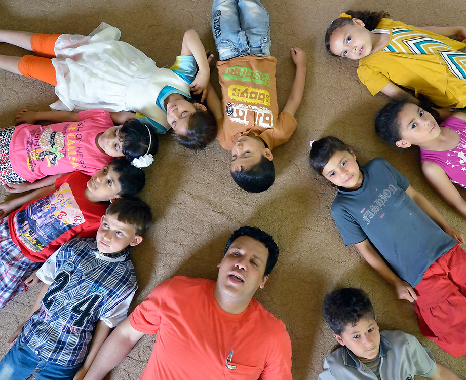 Emad Almoqari lies on the floor with a group of children in an activity at the Youth Empowerment Center in Beit Hanoun, Gaza. The program is supported by Caritas and DanChurchAid, a member of the ACT Alliance, and is designed to help children better cope with the trauma they experienced during the 2014 war.<br /> <br /> In the wake of that war between the government of Gaza and the government of Israel, ACT Alliance members are supporting health care, vocational training, rehabilitation of housing and water systems, psycho-social care, and other humanitarian actions throughout the besieged Palestinian territory.