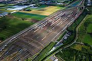 Nederland, Zuid-Holland, Zwijndrecht, 15-07-2012; Kijfhoek, rangeerterrein voor goederentreinen. Overzicht van de verdeelsporen met onder in beeld de railremmen..Kijfhoek huisvest Keyrail, exploitant Betuweroute en is in beheer bij ProRail. De Betuweroute, die begint als Havenspoorlijn op de Maasvlakte, verbindt via Kijfhoek de Rotterdamse haven met het achterland. Het rangeeremplacement dient voor het sorteren van goederenwagons waarbij gebruik gemaakt wordt van de zwaartekracht, het 'heuvelen': de wagons worden de heuvel opgeduwd, bij het de heuvel afrollen komen ze, door middel van wissels, op verschillende verdeelsporen. Railremmen zorgen voor het automatisch remmen van de wagons. Na het heuvelproces staan de nieuw samengestelde treinen op aparte opstelsporen..Kijfhoek, railway yard used by ProRail and Keyrail (Betuweroute operator). Kijfhoek connects via the Betuweroute (beginning as Havenspoorlijn on the Maasvlakte), through the port of Rotterdam with the hinterland. The shunting yard for sorting wagons makes use of gravity. The new trains are assembled on separate tracks..luchtfoto (toeslag), aerial photo (additional fee required).foto/photo Siebe Swart
