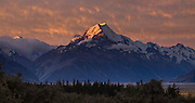 The last rays of sunset brighten clouds over Aoraki / Mount Cook (3755 meters or 12,349 feet) in Aoraki / Mount Cook National Park, South Island, New Zealand. In 1990, UNESCO honored Te Wahipounamu - South West New Zealand as a World Heritage Area. Panorama stitched from 2 overlapping photos.