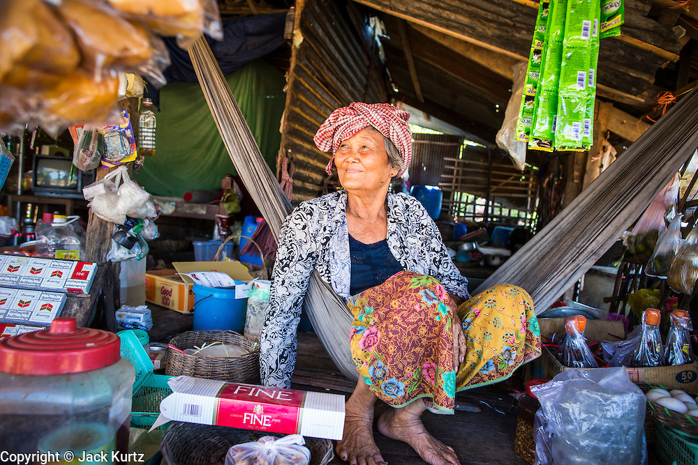 29 JUNE 2013 - BATTAMBANG, CAMBODIA:  A 77 year old woman who sells snack and drinks on the side of the bamboo train tracks near Battambang. The bamboo train, called a norry (nori) in Khmer is a 3m-long wood frame, covered lengthwise with slats made of ultra-light bamboo, that rests on two barbell-like bogies, the aft one connected by fan belts to a 6HP gasoline engine. The train runs on tracks originally laid by the French when Cambodia was a French colony. Years of war and neglect have made the tracks unsafe for regular trains.  Cambodians put 10 or 15 people on each one or up to three tonnes of rice and supplies. They cruise at about 15km/h. The Bamboo Train is very popular with tourists and now most of the trains around Battambang will only take tourists, who will pay a lot more than Cambodians can, to ride the train.       PHOTO BY JACK KURTZ
