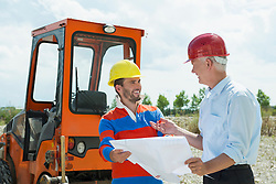 Building owner and construction worker discussing  construction plan