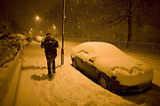 An early morning commuter makes his way home after his night shift in central London to his home nearby in Herne Hill, SE24 - a distance of approximately 6 miles. Trudging on foot through ever-deepening snow, the showers are still falling as he makes his way along the deserted street.  Street lighting makes this quiet landscape glow orange and we look down the road to see only a few parked cars at the kerbsides and the tracks of a few others that have already driven along. Thousands of snowflakes are fluttering to the ground, settling on this part of London's inner-city - an unusual event - and the  heaviest precipitation for 18 years.