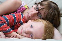 Mother and son lying on the sofa having a cuddle,