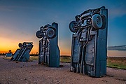 "Carhenge sunrise. Carhenge replicates England's Stonehenge using vintage American automobiles, near Alliance, Nebraska, in the High Plains region, USA. After studying Stonehenge in England, years later, Jim Reinders recreated the physical size and placement of Stonehenge's standing stones in summer 1987, helped by 35 family members. Reinders said, ""It took a lot of blood, sweat, and beers."" Carhenge was built as a memorial to Reinders' father. 39 automobiles were arranged in the same proportions as Stonehenge with the circle measuring a slightly smaller 96 feet (29m) in diameter. Some autos are held upright in pits five feet deep, trunk end down, while other cars are placed to form the arches and welded in place. All are covered with gray spray paint. The heel stone is a 1962 Cadillac. Reinders donated Carhenge to the Friends of Carhenge, who gifted it to the Citizens of Alliance in 2013. Additional sculptures have been erected in the Car Art Reserve, where Reinders' ""Ford Seasons"" is comprised of four Fords, inspired by Vivaldi's Four Seasons. Also, 29-year-old Canadian Geoff Sandhurst sculpted a spawning salmon."
