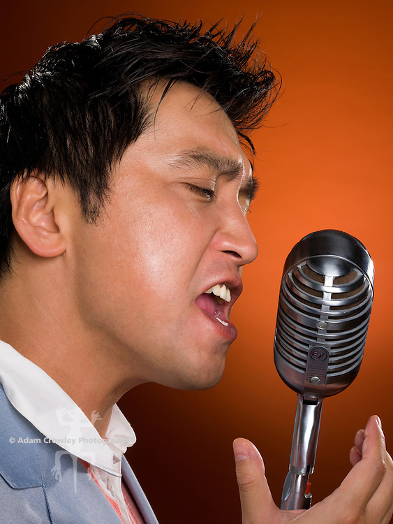Asian man speaks into a vintage microphone