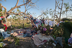 October 7, 2016 - Port Salute, Haiti - Victims of hurricane Matthew hang their belongings on a fallen tree in a village near Port Salute after hurricane Matthew hits the area, on October 7, 2016. Hurricane Matthew killed almost 900 people and displaced tens of thousands in Haiti before plowing northward on Saturday just off the southeast U.S. coast, where it caused major flooding and widespread power outages. (Credit Image: © Bahare Khodabande/NurPhoto via ZUMA Press)
