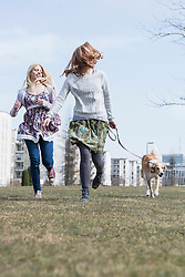 Two friends running in park with dog, Munich, Bavaria, Germany