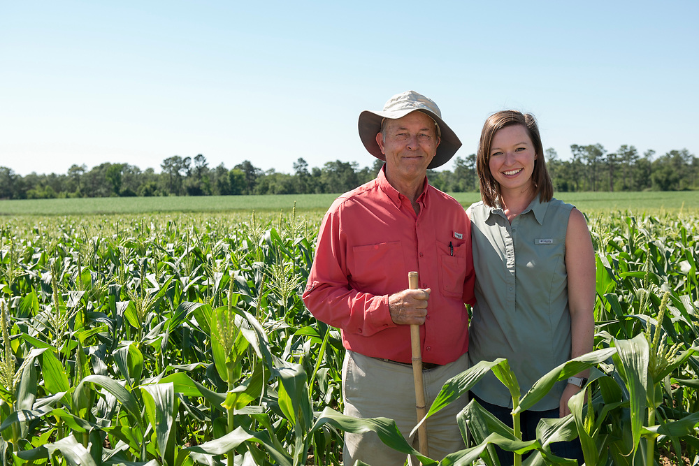 Casey Cox and her dad, Glenn, in a corn field. Casey is becoming the sixth generation to farm the family's land in Mitchell County, Georgia.