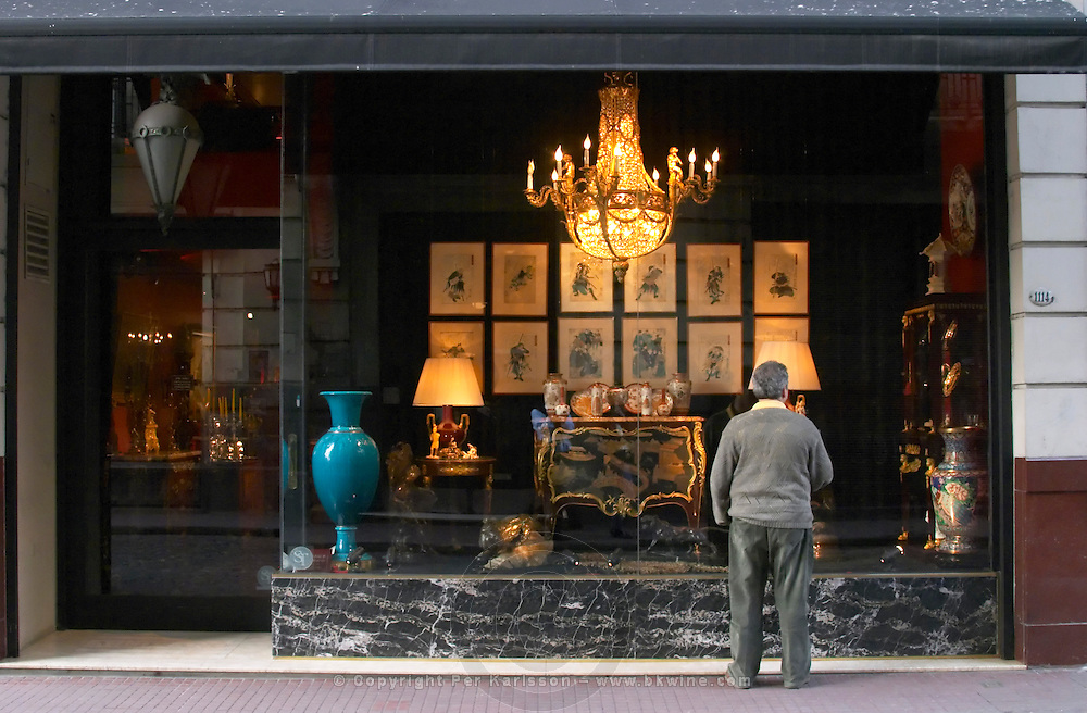 Interior of an antique shop in the San Telmo district around Plaza Dorrego Square, A man with his back to the camera in a grey sweater standing outside an antique shop looking at the things displayed in the shop window: vase, candelabra, crystal chandelier, chest of drawers in lacquer paintings... Calle Defensa Defence street Buenos Aires Argentina, South America