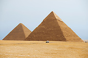 Two of the great pyramids on the Giza Plateau with a car in front showing scale of these huge structures.