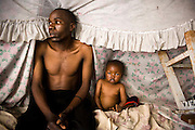 KENYA. Nairobi. Father and son living in the slum of Kibera. His wife had a new born baby who was very sick, but they could not afford medication...Kibera is Africa's largest slum and it is located in Nairobi, Kenya. It houses one million people squeezed into less than a square mile. Most people living in Kibera have little or no access to basic necessities, such as electricity, clean water, toilet facility and sewage disposal. The combination of poor nutrition and lack of sanitation accounts for many illnesses and deaths.