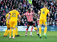 Lincoln City's John Akinde shields the ball from under pressure from Northampton Town's Jordan Turnbull, left, John-Joe O'Toole, centre, and Charlie Goode<br /> <br /> Photographer Andrew Vaughan/CameraSport<br /> <br /> The EFL Sky Bet League Two - Lincoln City v Northampton Town - Saturday 9th February 2019 - Sincil Bank - Lincoln<br /> <br /> World Copyright © 2019 CameraSport. All rights reserved. 43 Linden Ave. Countesthorpe. Leicester. England. LE8 5PG - Tel: +44 (0) 116 277 4147 - admin@camerasport.com - www.camerasport.com