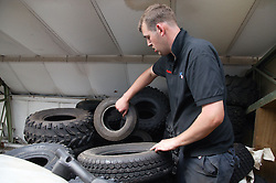 Man with Cerebral Palsy working as mechanic; sorting through tyres from all terrain vehicles in workshop,