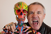 """Damien Hirst Portrait sticks tongue outwith his artwork.""""St Elmo's Fire"""".2008.Household gloss on plastic skeleton.1700 x 425 x 435 mm.© Damien Hirst. All rights reserved, DACS 2010.Photographed in his Chalford Studio, near Stroud, Gloucestershire"""