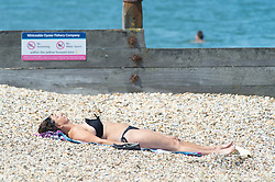 © Licensed to London News Pictures 22/07/2021. Whitstable, UK. A woman sunbathing on the beach. Another hot heatwave day in the UK as people enjoy a day out at Whitstable in Kent. Photo credit:Grant Falvey/LNP