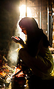 """9th April 2015, New Delhi, India. Women pray at a shrine dedicated to Djinn worship in the ruins of Feroz Shah Kotla in New Delhi, India on the 9th April 2015<br /> <br /> PHOTOGRAPH BY AND COPYRIGHT OF SIMON DE TREY-WHITE a photographer in delhi<br /> + 91 98103 99809. Email: simon@simondetreywhite.com<br /> <br /> People have been coming to Firoz Shah Kotla to leave written notes and offerings for Djinns in the hopes of getting wishes granted since the late 1970's. Jinn, jann or djinn are supernatural creatures in Islamic mythology as well as pre-Islamic Arabian mythology. They are mentioned frequently in the Quran  and other Islamic texts and inhabit an unseen world called Djinnestan. In Islamic theology jinn are said to be creatures with free will, made from smokeless fire by Allah as humans were made of clay, among other things. According to the Quran, jinn have free will, and Iblīs abused this freedom in front of Allah by refusing to bow to Adam when Allah ordered angels and jinn to do so. For disobeying Allah, Iblīs was expelled from Paradise and called """"Shayṭān"""" (Satan).They are usually invisible to humans, but humans do appear clearly to jinn, as they can possess them. Like humans, jinn will also be judged on the Day of Judgment and will be sent to Paradise or Hell according to their deeds. Feroz Shah Tughlaq (r. 1351–88), the Sultan of Delhi, established the fortified city of Ferozabad in 1354, as the new capital of the Delhi Sultanate, and included in it the site of the present Feroz Shah Kotla. Kotla literally means fortress or citadel."""