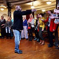 Nederland, Amsterdam , 15 december 2013.<br /> Herdenking Mandela.<br /> Prinses Beatrix is rond het middaguur aangekomen bij de Stadsschouwburg in Amsterdam. Zij woont daar het Nationaal Eerbetoon Samen door Mandela bij. Burgemeester Eberhard van der Laan van Amsterdam ontving de prinses op de rode loper voor de schouwburg.<br /> Voorafgaand aan het programma heeft Beatrix een ontmoeting met de initiatiefnemers van het eerbetoon, onder wie Conny Braam (oud-voorzitter Anti Apartheidsbeweging Nederland), Melle Daamen (directeur Stadsschouwburg) en zangeres en actrice Gerda Havertong. Namens het kabinet is minister Jet Bussemaker van Onderwijs, Cultuur en Wetenschap aanwezig.De aankomst van de prinses werd begeleid door een Afrikaanse drumband. Tientallen belangstellenden stonden langs de loper en voor de schouwburg mee te klappen, dansen en sommigen zongen 'Mandela! Mandela!'.<br /> Op de foto: in de Stadsschouwburg zongen diverse gospelzangers  liederen ter ere van de overleden Nelson Mandela.<br /> Foto:Jean-Pierre Jans