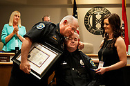 21 JUNE 2017 -- HAZELWOOD, Mo. -- Hazelwood police officer Craig Tudor (center) is presented with a Law Enforcement Purple Heart award by Hazelwood police chief Gregg Hall (left) as Tudor's wife Christine Tudor (right) watches during a meeting of the Hazelwood City Council Wednesday, June 21, 2017. Tudor was seriously injured and left paralyzed following an auto accident while responding to a call for an an officer-in-need-of-aid Aug. 25, 2016. Photo © copyright Sid Hastings.