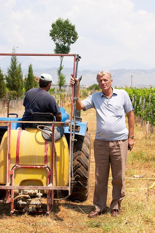 Gezim Coku, agronomist and vineyard manager. In the vineyard with a vineyard tractor and vineyard worker. Spraying tractor. Kantina Miqesia or Medaur winery, Koplik. Albania, Balkan, Europe.