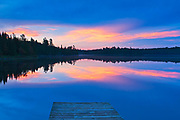Dock and reflection on Lyons Lake at dawn<br />Whiteshell Provincial Park<br />Manitoba<br />Canada