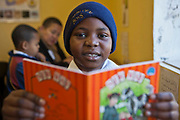 A young African school-child proudly holds his reading book and smiles in in a class room in Zonnebloem School, Cape Town, South Africa.  He is learning to read independently.  The book has been provided provided to the school by Shine Centre which is a charity that aims to address the high illiteracy rate in South Africa by improving literacy levels among children in schools and disadvantaged communities.