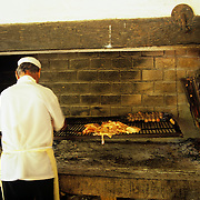 South America, Uruguay, Carrau winery, Montevideo, A chef prepares a lunch of meat and fowl.