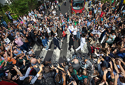 © Licensed to London News Pictures. 08/08/2019. London, UK. A Beatles tribute band called the 'Fab Four' are mobbed by fans as they recreate the famous album cover photograph at the zebra crossing outside the Abbey Road studios in north London. The Beatles were photographed for the Abbey Road album cover 50 years ago today. Photo credit: Peter Macdiarmid/LNP