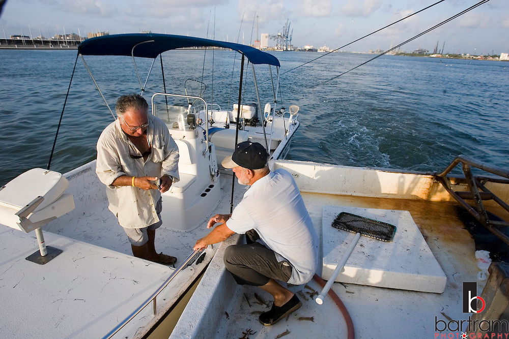 KEVIN BARTRAM/The Daily News.Jerome Kunz, right, sells live shrimp to a fisherman in the Galveston Ship Channel on Wednesday, July 12, 2006. Kunz often sells bait to passing fishermen but the majority of his catch is sold through a local bait camp.