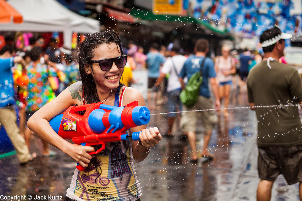 13 APRIL 2014 - BANGKOK, THAILAND: A tourist with a large squirt gun on Khao San Road in Bangkok's backpacker district on the first day of Songkran. Songkran is celebrated in Thailand as the traditional New Year's Day from 13 to 16 April. Songkran is in the hottest time of the year in Thailand, at the end of the dry season and provides an excuse for people to cool off in friendly water fights that take place throughout the country. Songkran has been a national holiday since 1940, when Thailand moved the first day of the year to January 1.    PHOTO BY JACK KURTZ