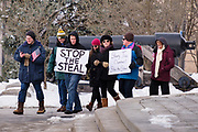 "02 JANUARY 2021 - DES MOINES, IOWA: People walk past the front of the Iowa State Capitol. About 30 people marched around the Iowa State Capitol Saturday afternoon to protest the outcome of the November 3 general election in the United States. They are a part of the ""Stop the Steal"" movement which maintains that the election was stolen from Donald Trump by massive voter fraud. There is no evidence supporting their conspiracy theory. This is the 9th week Donald Trump supporters have marched around the Capitol. They've been there every week since the Nov. 3 election. More than 1,000 people showed up the first week, but the crowd has gotten smaller every week.     PHOTO BY JACK KURTZ"