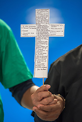 13 December 2019, Madrid, Spain: Faith-based organizations gather for a vigil, as COP25 is about to draw to a close, praying that negotiations will bear fruit, bringing about urgent and just action to find a way out of the climate crisis. Here, two people join in holding a cross, which is a replica of a much larger cross from the Lutheran Cathedral of El Salvador, referred to as 'La Cruz Subversiva'. On the cross are written testimonies of people in El Salvador noting down the oppressions they suffer in their daily lives. The cross has a special history, in that it was confiscated by 'El Ejército' (The People's Revolutionary Army) in November 1989, while El Salvador was living through war.