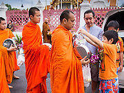 """21 JULY 2013 - BANGKOK, THAILAND:   A family prays with Buddhist monks after making merit at Wat Benchamabophit on the first day of Vassa, the three-month annual retreat observed by Theravada monks and nuns. On the first day of Vassa (or Buddhist Lent) many Buddhists visit their temples to """"make merit."""" During Vassa, monks and nuns remain inside monasteries and temple grounds, devoting their time to intensive meditation and study. Laypeople support the monastic sangha by bringing food, candles and other offerings to temples. Laypeople also often observe Vassa by giving up something, such as smoking or eating meat. For this reason, westerners sometimes call Vassa the """"Buddhist Lent.""""      PHOTO BY JACK KURTZ"""