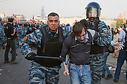 Moscow, Russia, 06/05/2012..A riot policeman strikes out at photographers while seizing a protestor by the hair as police arrest protestors at an opposition demonstration against Russian Presidential election results on the eve of Vladimir Putin's inauguration as President.