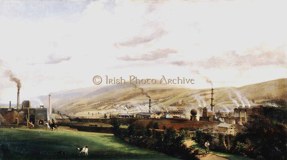 Industrial landscape, Wales. Ironworks clearly showing blast furnaces with flames spouting from their tops. Foreground shows contrast of green field and garden of ironmaster's house. Artist,  Penry Williams (1798-1885). Private collection.
