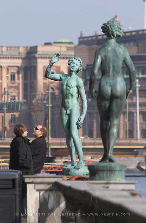 In the Garden of Stadshuset, the Stockholm Town Hall. Two tourist a man and a woman and two bronze statues: Song by Carl Eldh a naked man holding a bunch of grapes and of a naked woman by Carl Eldh Stockholm, Sweden, Sverige, Europe
