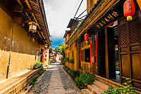 Back lanes with buildings made of mud brick (adobe) in the market town of Shaxi, on the Tea Horse Caravan Road, which links Southern Yunnan to Tibet and Burma and retains its position as one of the best preserved historic market hubs today. Yunnan Province, China.