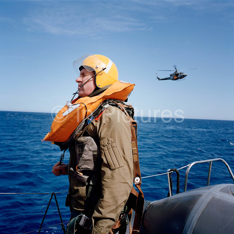 Pilot of the Red Arrows, UK's RAF aerobatic team readies himself before a simulated ditching in the cold sea during exercise. We see the pilot, looking nervous - happier in the air - wearing survival gear, Flt. Lt. Steve Underwood of the elite team, about to plunge into the cold Mediterranean waters for his annual Wet Drill exercise during Spring training in Cyprus. The rehearsal is to practise a helicopter recovery after a fast-jet ejection over the sea. His RAF-issue life vest (containing a vital life-raft) will inflate when in contact with the salt water and helps him stay afloat before the helicopter pick-up. This yearly event is required of all flying personnel to ensure that any accident over water can reach a positive outcome - by the rescuing of an expensively-trained pilot or navigator.
