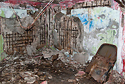 An abandoned bunker in disrepair full of debris.