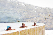 Tourists wet themselves at the pools in Pamukkale. The hard, white mineral deposits, which from a distance resemble snow, are caused by the high mineral content of the natural spring water which runs down the cliff and congregates in warm pools on the terraces. This is such a popular tourist attraction that strict rules had to be established in order to preserve its beauty, which include the fact that visitors may no longer walk on the terraces. Those who want to enjoy the thermal waters, however, can take a dip in the nearby pool, littered with fragments of marble pillars.