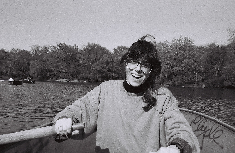 1. When was this photo taken?<br /> <br /> mid-1980s<br /> <br /> 2. Where was this photo taken?<br /> <br /> Central Park, New York City<br /> <br /> 3. Who took this photo?<br /> <br /> Jeffrey Levin<br /> <br /> 4. What are we looking at here?<br /> <br /> Although this is on Nancy Kaye's roll, this is a photo that I (Jeffrey Levin) took of my now-wife, Nancy, when we were still living in New York City and dating. She is rowing in a rowboat on the lake in Central Park on one of our weekend outings together.<br /> <br /> 5. How does this old photo make you feel?<br /> <br /> The image of Nancy smiling and so clearly happy gives me great pleasure, returning to me an afternoon long ago that we shared with such delight, just being in each other's company.<br /> <br /> 6. Is this what you expected to see?<br /> <br /> I had no idea what to expect.<br /> <br /> 7. What kind of memories does this photo bring back?<br /> <br /> It recalls for me my life in New York and the early days of my relationship with Nancy.<br /> <br /> 8. How do you think others will respond to this photo?<br /> <br /> They will see a young woman, vigorous and joyful, enjoying the happiness of the moment.