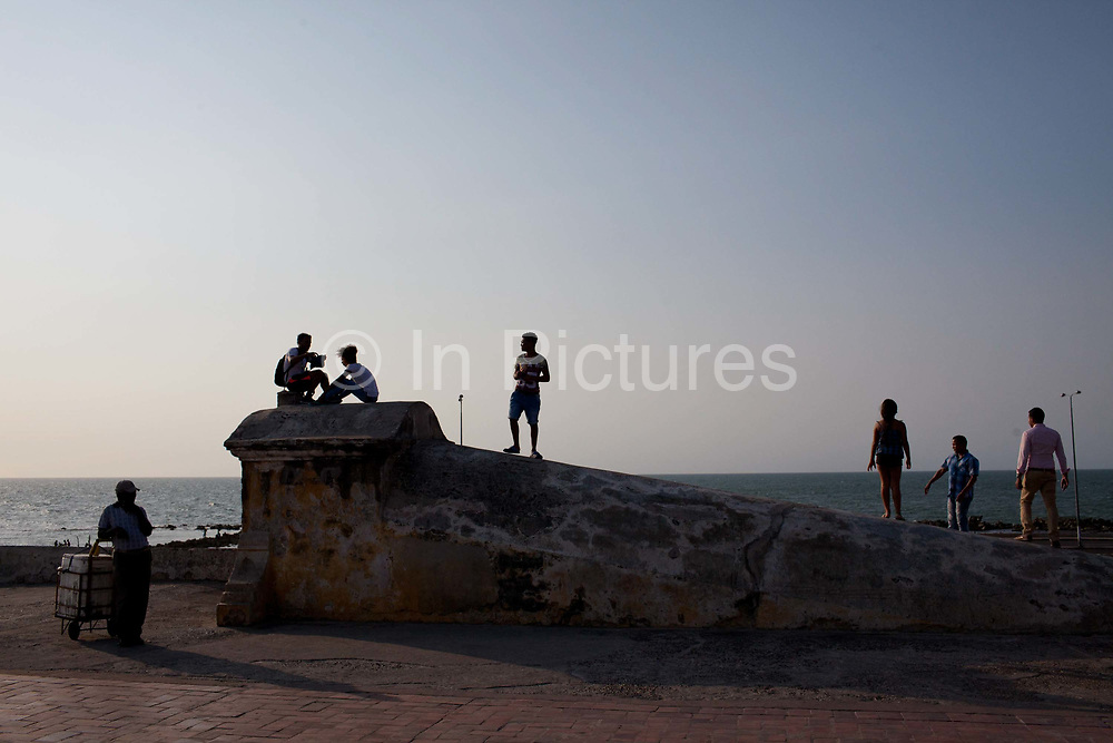 People standing on the city walls, silhouette, street scene and historic Colonial architecture. Cartagena historic old city UNESCO World heritage site, capital of Bolivar department, Colombia.