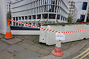 Construction landscape of tape and newly-painted concrete barrier on City street corner. With cones supporting the red and white striped tape, we see a makeshift sign telling passers-by of freshly painted surfaces. In the background is a future corporate development that has yet to appear from behind the construction hoarding in the City of London, the capital's financial heart, founded by the Romans in 43AD.