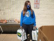 """11 MAY 2020 - DES MOINES, IOWA: GRACE OSTRANDER holds food packages while she waits for clients at a """"no touch"""" emergency food pantry at DSM First Church in Des Moines. The emergency pantry at DSM First Church expanded from distribution one day a week to three days per week after the COVID-19 pandemic forced the closure of many Iowa businesses. Food banks and emergency pantries in Iowa continue to see increased demand for services, even though the governor is reopening the state's economy. Iowa's unemployment rate for April hasn't been released yet, but based on national trends, it is expected to soar to well over 10% from 3.8& in March. COVID-19 infections continue to skyrocket. On Monday, 11 May, the governor announced that 12,373 people tested positive for coronavirus (SAR-CoV-2) and  271 had died.             PHOTO BY JACK KURTZ"""