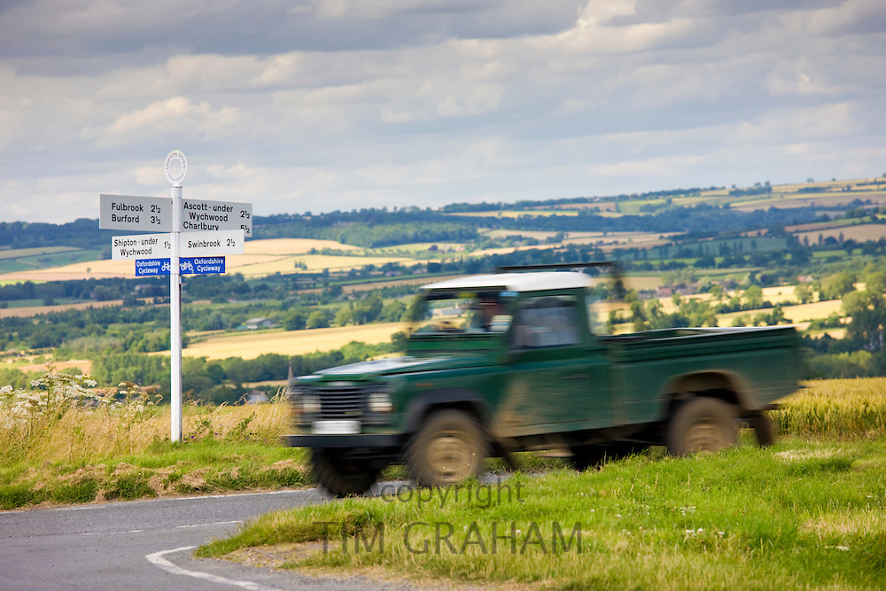 Farmer's Land Rover passing signpost at rural crossroads in The Cotswolds, Oxfordshire, UK